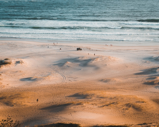 Minuscole persone che si godono la giornata in spiaggia