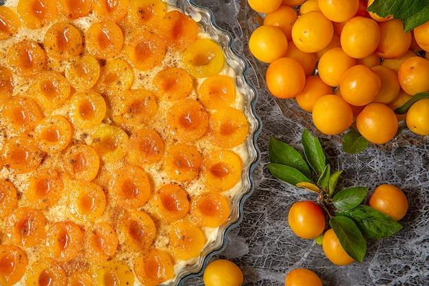 Mirabelle di prugne gialle. cucinare la torta di prugne. impasto in una teglia e prugna affettata. stagione estiva della frutta.