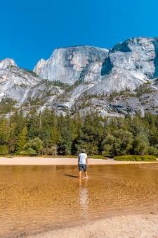 Mirror lake, un giovane in camicia bianca che cammina lungo l'acqua del lago e il sole. california, stati uniti