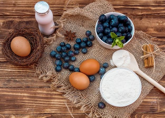 Mirtilli con la foglia nella ciotola bianca, farina nella ciotola, cucchiaio di legno, yogurt, uova sui precedenti di legno marroni