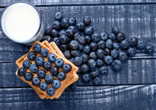 Mirtilli e cialde su legno blu con un bicchiere di latte