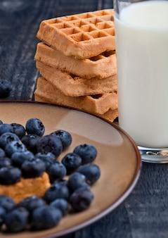 Mirtilli e cialde sul piatto con un bicchiere di latte