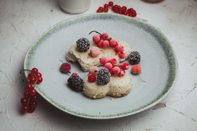 Mirtilli in un piatto con le more e la vista dell'angolo alto del biscotto su un strutturato bianco