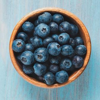 Mirtilli in una ciotola di legno sul tavolo di legno blu brillante.
