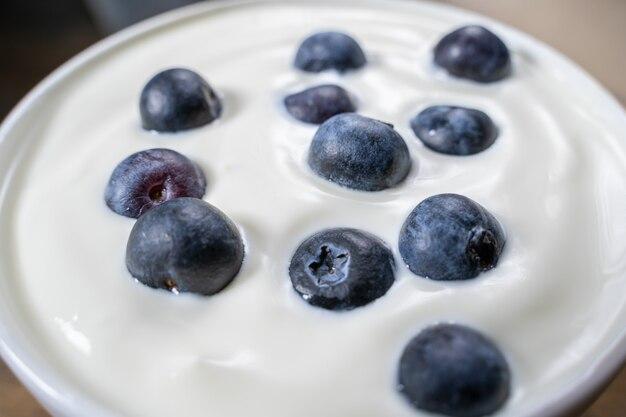 Mirtilli in yogurt organico, fine sulla foto