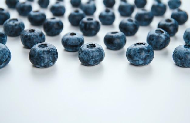 Mirtilli maturi su uno spazio bianco della copia del fondo. grandi bacche blu.