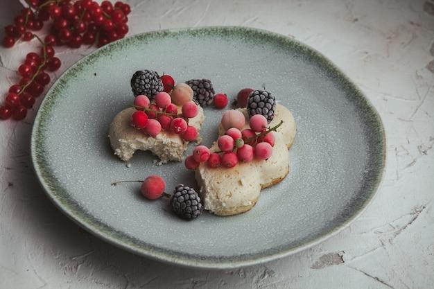 Mirtilli rossi di vista dell'angolo alto in piatto con le more, biscotto su strutturato bianco.
