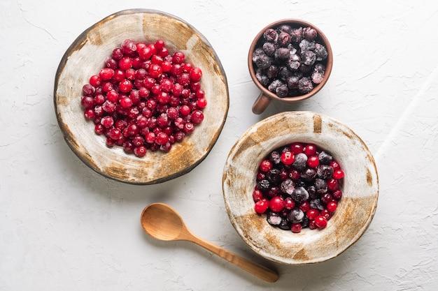 Mirtilli rossi e aronia congelati in piatti di argilla su sfondo chiaro