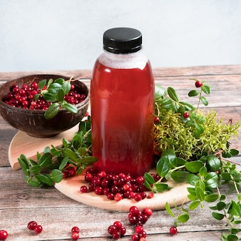 Mirtilli rossi e succo di mirtillo rosso in una bottiglia su fondo di legno