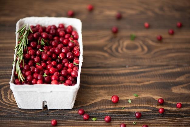 Mirtilli rossi maturi freschi in una scatola del mestiere su un tavolo di legno