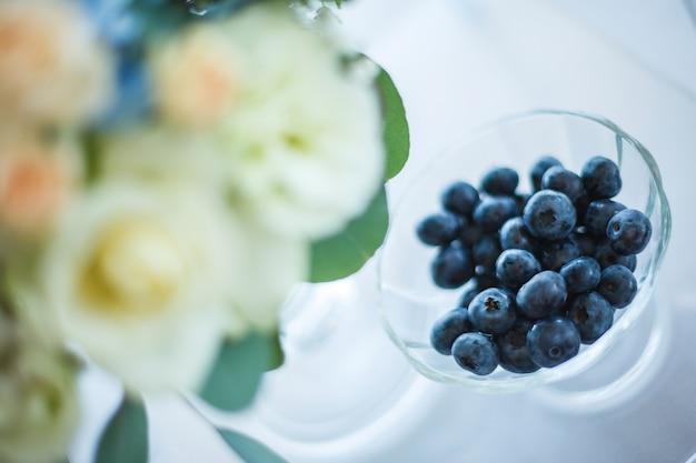Mirtillo in vetro e fiori bianchi e blu nella decorazione di nozze