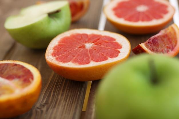 Miscela dei frutti affettati freschi su un fondo di legno. foto con profondità di campo.