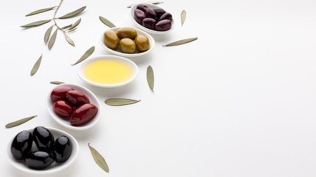 Miscela dell'angolo alto delle olive e dell'olio viola verdi rossi neri con lo spazio della copia