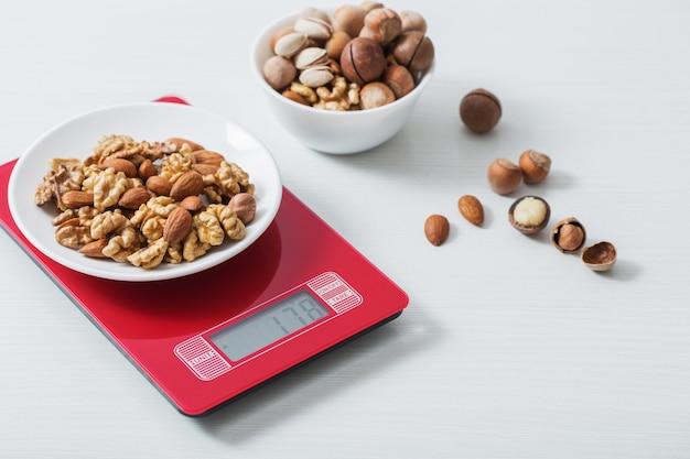 Miscela delle noci differenti sulla scala della cucina su una tabella bianca