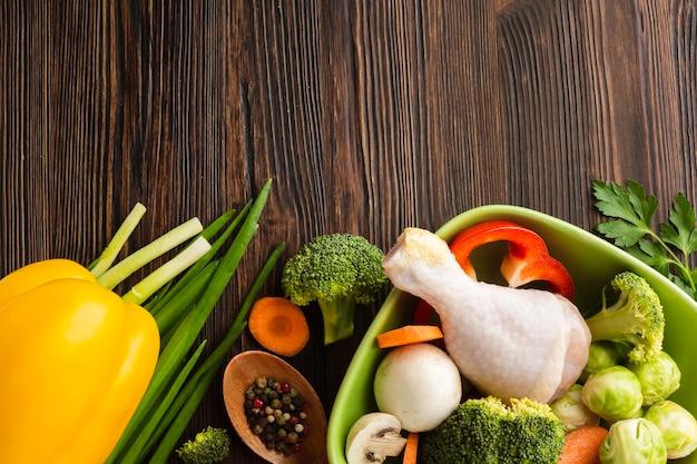 Miscela delle verdure di vista superiore e bacchetta di pollo in ciotola con lo spazio della copia