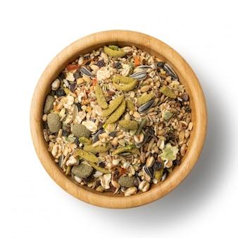 Miscela di cibo secco per roditori per topo, coniglio o degu in ciotola di legno isolata sulla vista superiore del fondo bianco.