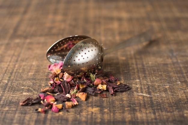 Miscela essiccata di tè alle erbe con frutti di bosco con petali versati dal colino del tè sulla tavola di legno
