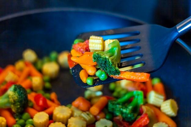Misto di verdure fritte in padella. cucinare verdure surgelate.