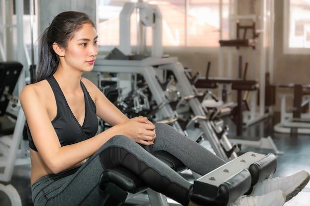 Misura della donna dell'asia e sorridere sano in palestra dopo l'allenamento.
