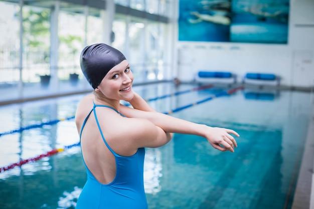 Misura la donna allungando le braccia in piscina