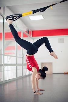 Misura la giovane donna graziosa che fa gli esercizi di allungamento