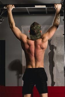 Misura le dita dei piedi per escludere l'esercizio di allenamento delle barre di pull-up dell'uomo in palestra