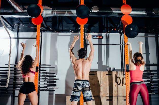 Misura, sport e concetto di esercitazione - la gente con le palle mediche che si prepara nella palestra