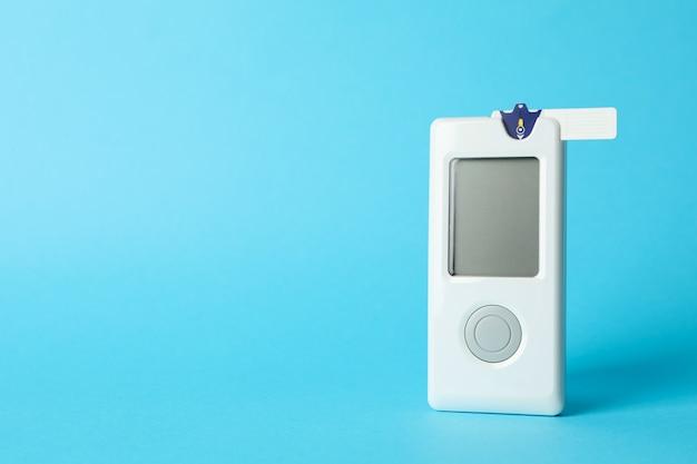 Misuratore di glucosio nel sangue su sfondo blu, spazio per il testo