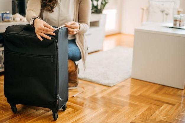 Misurazione del bagaglio a mano con nastro di misurazione prima di andare in vacanza.