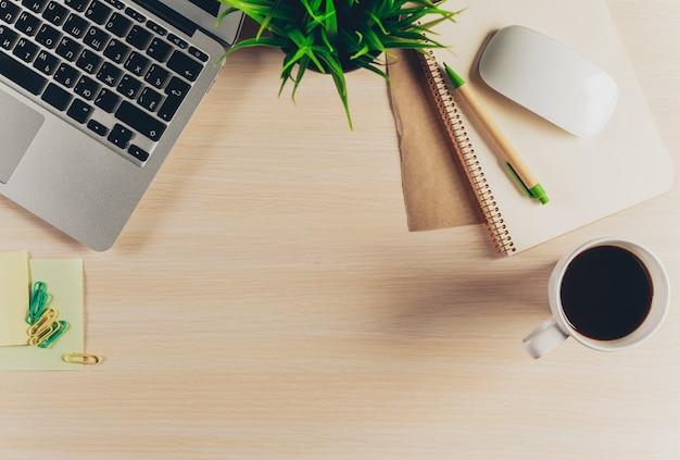 Mix di articoli per ufficio e gadget su uno sfondo di tavolo in legno.