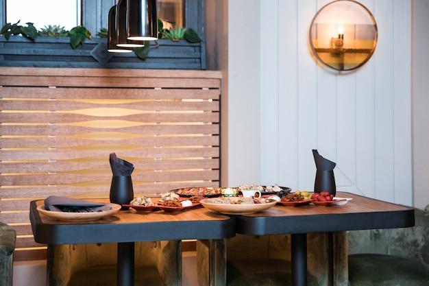 Mix di diversi snack e stuzzichini. tapas spagnole su uno spazio di pietra nera. bar. spazio per il testo. gastronomia, panini, olive, salsiccia, acciughe, formaggio, prosciutto, pepe, pomodori. vista dall'alto