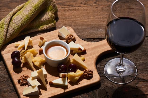 Mix di formaggio di parmigiano, mozzarella, camembert su una tavola di legno e un bicchiere di vino rosso