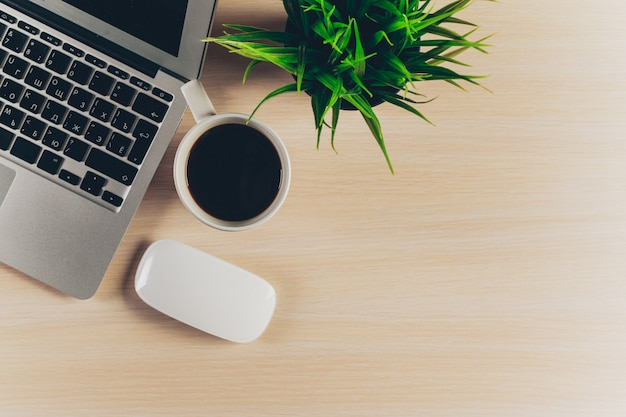 Mix di forniture per ufficio e gadget su uno sfondo di tavolo in legno.
