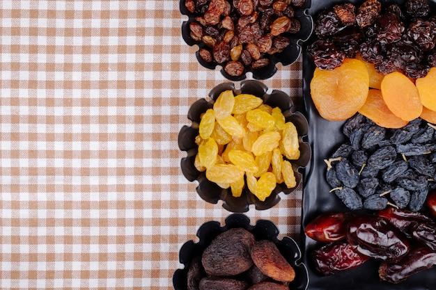 Mix di frutta secca date uvetta albicocche e ciliegie su un vassoio nero e in mini scatole di latta sulla tovaglia plaid con spazio di copia vista dall'alto