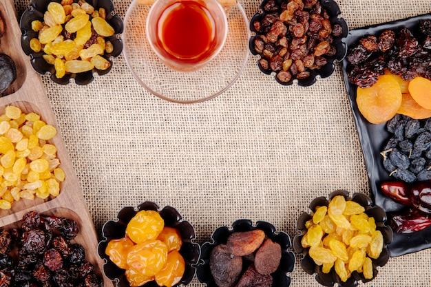 Mix di frutta secca datteri uvetta albicocche e ciliegie in mini scatole di latta servite con tè su tela di sacco con copia spazio vista dall'alto