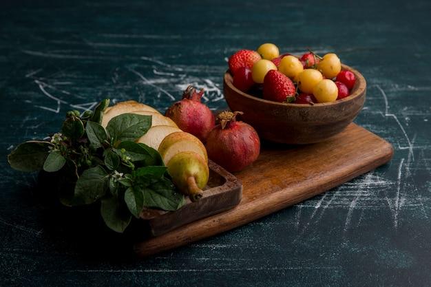 Mix di frutta su un piatto di legno isolato su uno spazio blu