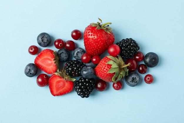 Mix di frutti di bosco freschi su sfondo blu, vista dall'alto