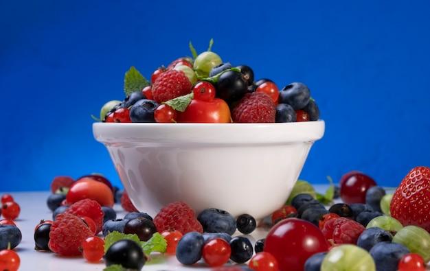Mix di frutti di bosco su sfondo blu, raccolta di fragole, mirtilli, lamponi e mora