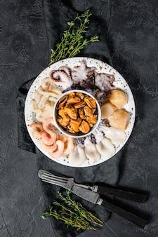 Mix di frutti di mare bolliti, cocktail di mare. sfondo nero. vista dall'alto