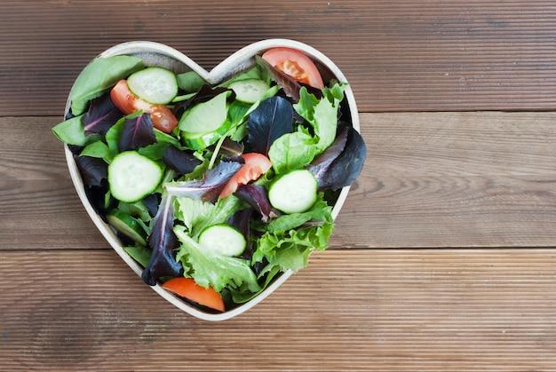 Mix di insalata verde fresca nel piatto a forma di cuore.