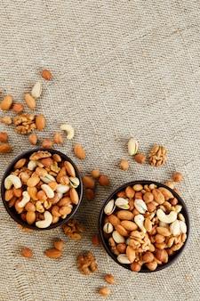 Mix di noci varie in una tazza di legno contro il tessuto di tela da imballaggio. noci come struttura e sfondo, macro. vista dall'alto.