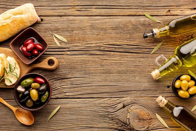 Mix di olive in ciotole bottiglie di olio d'oliva e pane con copia spazio