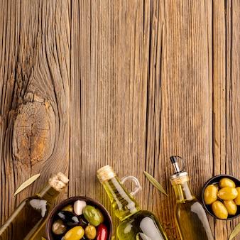 Mix di olive in ciotole e bottiglie di olio d'oliva con spazio di copia