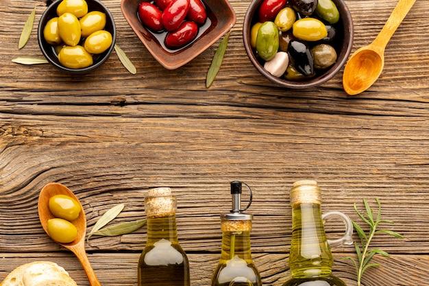 Mix di olive in ciotole e bottiglie di olio