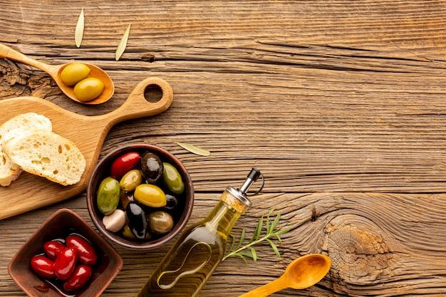 Mix di olive piatte con olio e copia spazio