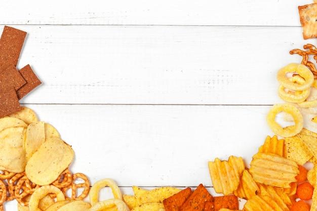 Mix di snack: salatini, crackers, patatine e nachos su sfondo bianco