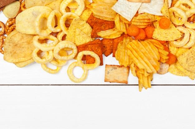 Mix di snack: salatini, crackers, patatine e nachos sul tavolo