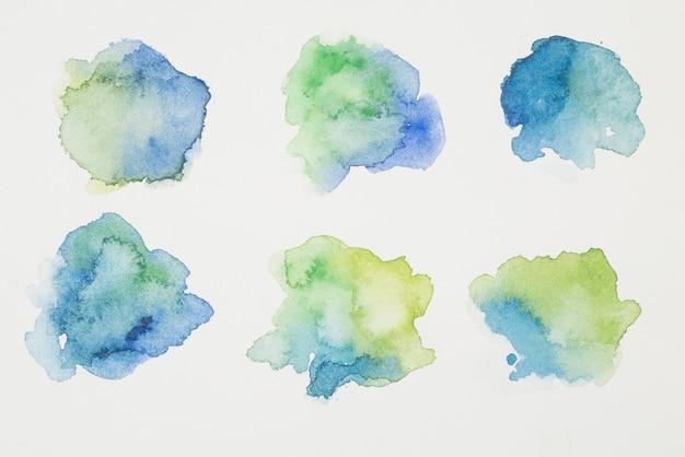 Mix di vernici blu, verdi e gialle su carta bianca