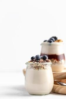 Mix di yogurt vista frontale con frutta, avena e marmellata