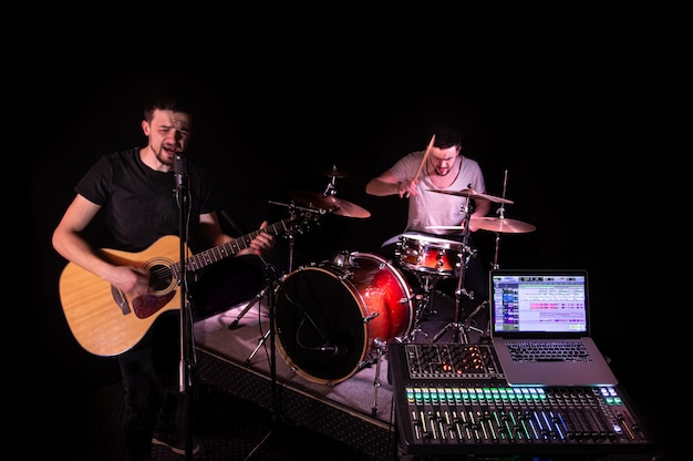 Mixer digitale in uno studio di registrazione, con un computer per la registrazione di musica. in sottofondo, i musicisti suonano strumenti musicali. il concetto di creatività e spettacolo.